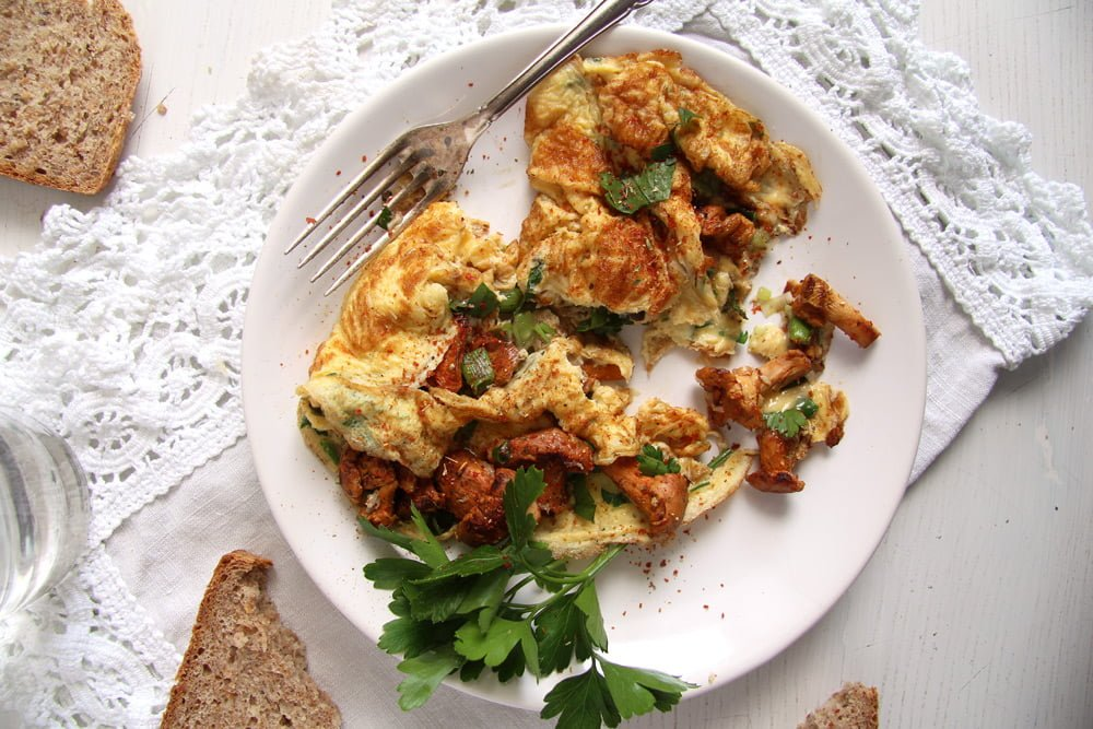 plate of chanterelle omelet with herbs on a white tablecloth