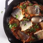 trout stew with tomatoes being served from the pan