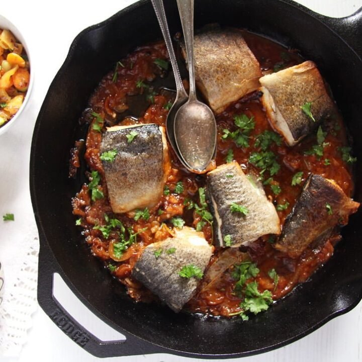 stewed trout with tomatoes in a skillet served with polenta in a bowl