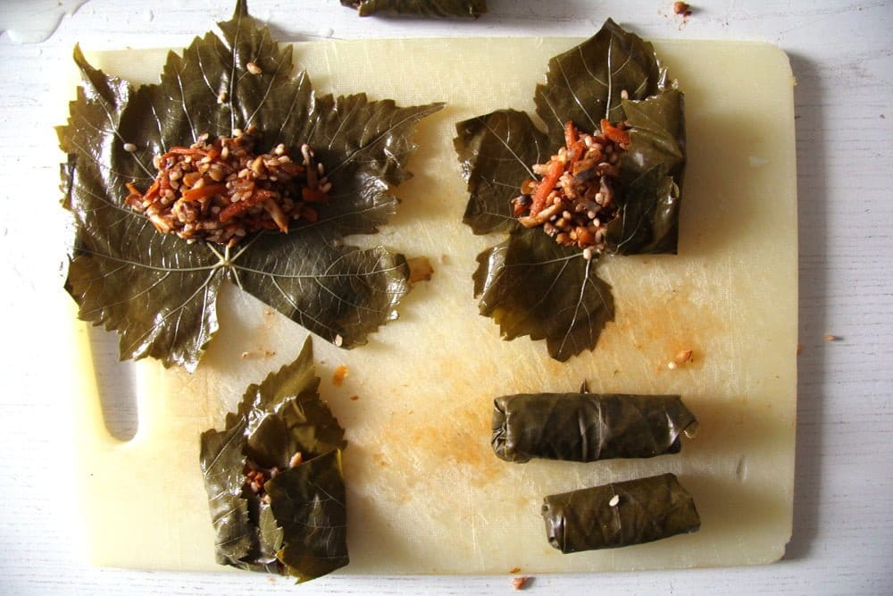 stuffing vine leaves with a mixture of rice and vegetables