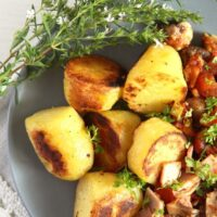 fried gypsy potatoes with bacon on a gray plate with thyme