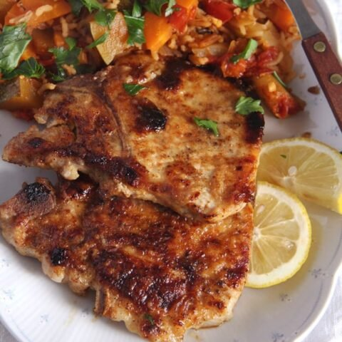 pork chop marinated in milk served with rice and lemon slices