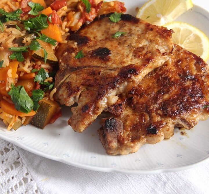 pork chops in milk marinade served with rice on a platter