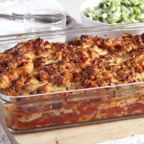 casserole dish with turkey lasagna on a wooden board
