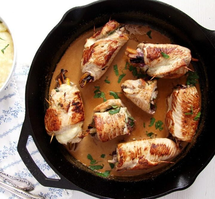 roulades of turkey with sauce in a cast iron pan