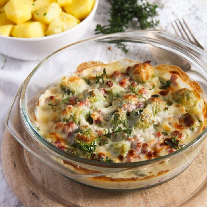 creamy cheesy brussels sprouts casserole with parmesan being served