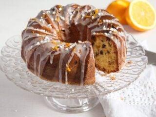 orange raisin bundt cake with chocolate chips on a tall platter