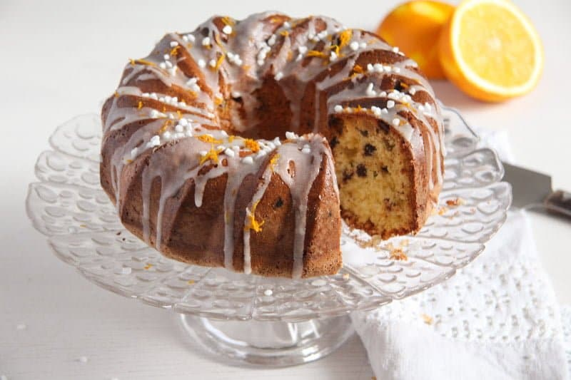 orange raisin bundt cake with chocolate chips on a tall platter