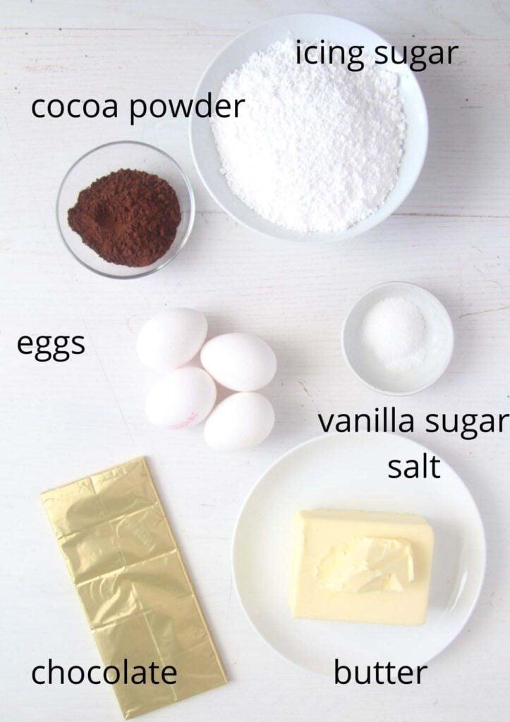 icing sugar, cocoa, eggs, vanilla sugar, salt, chocolate, butter arranged on the table.
