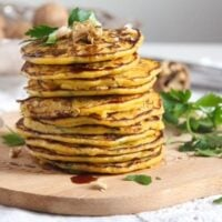 butternut squash fritters stapled on a wooden board with walnuts on top