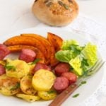 slice of pumpkin, potatoes and sausages arranged on a plate
