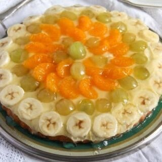 pudding tart with bananas, mandarins and grapes on a vintage platter