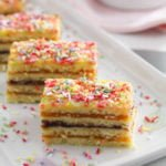 small squares of harlequin cake sprinkled with colorful sprinkles