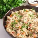 chicken pilaf sprinkled with parsley in a brown dish