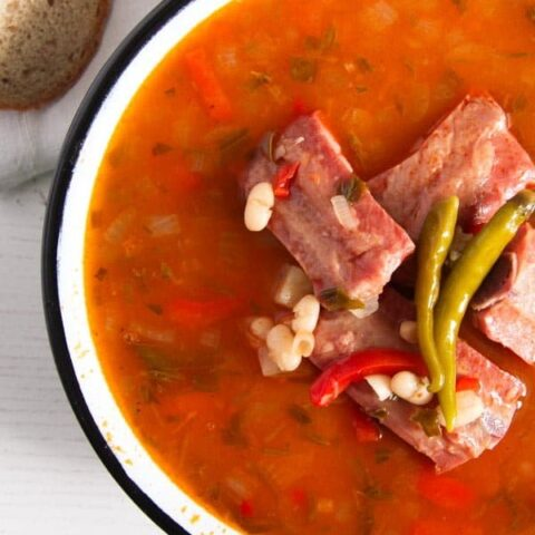 small ribs on top of a bowl or red soup with white beans