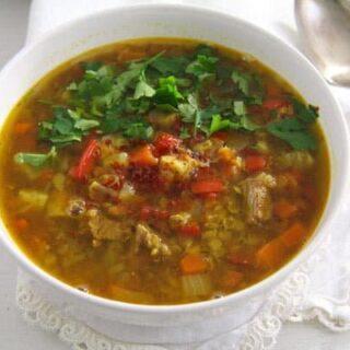 yellow lentil soup in a white bowl