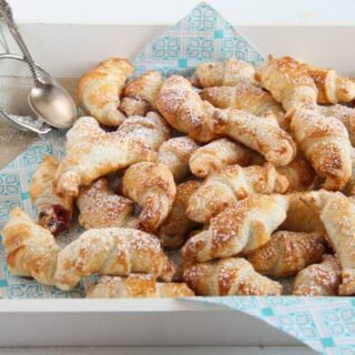 dozens of mini croissants with jam on a blue napkin