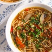 mushroom noodle soup sprinkled with herbs in a white bowl