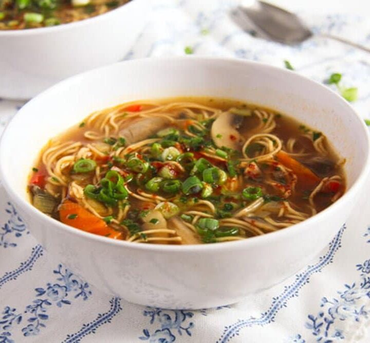 spicy mushroom noodles soup with herbs served in a white bowl