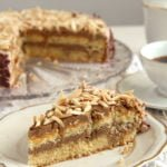 sliced polish coffee cake topped with roasted almonds on a vintage plate