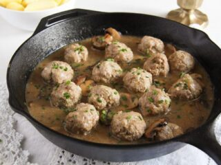 polish meatballs in mushroom sauce cooked in a cast-iron skillet
