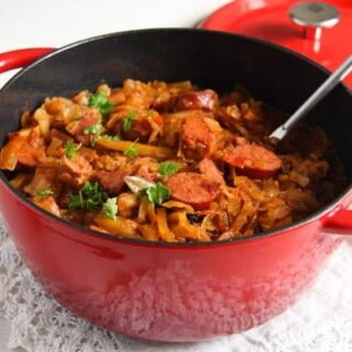 bigos with sauerkraut, pork and sausages in a red pot