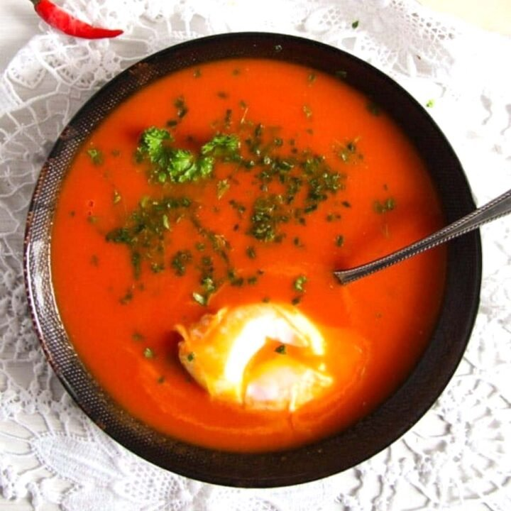black bowl with red tomato soup, green parsley and a poached egg.