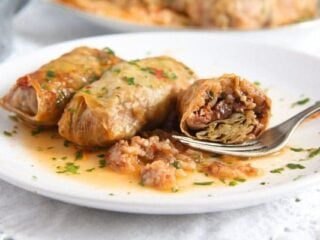 sour cabbage rolls eaten with a fork from a white plate