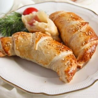 ham and cheese puff pastry croissants on a small vintage plate