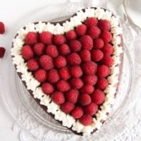 heart-shaped cheesecake for mother's day with a few raspberries beside it and a cup of coffee.