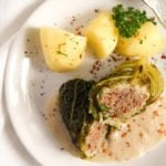 savoy cabbage rolls served with potatoes and white sauce