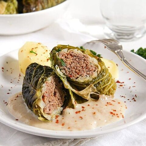 stuffed savoy cabbage rolls with potatoes and sauce on a plate