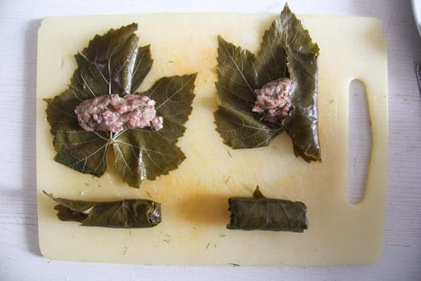 vine leaves on a board being filled with meat and rolled