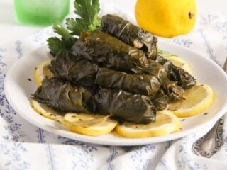 fish stuffed vine leaves with lemon slices on a white plate