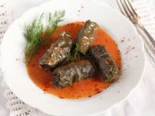 four rolls of grape leaves in a plate with sauce