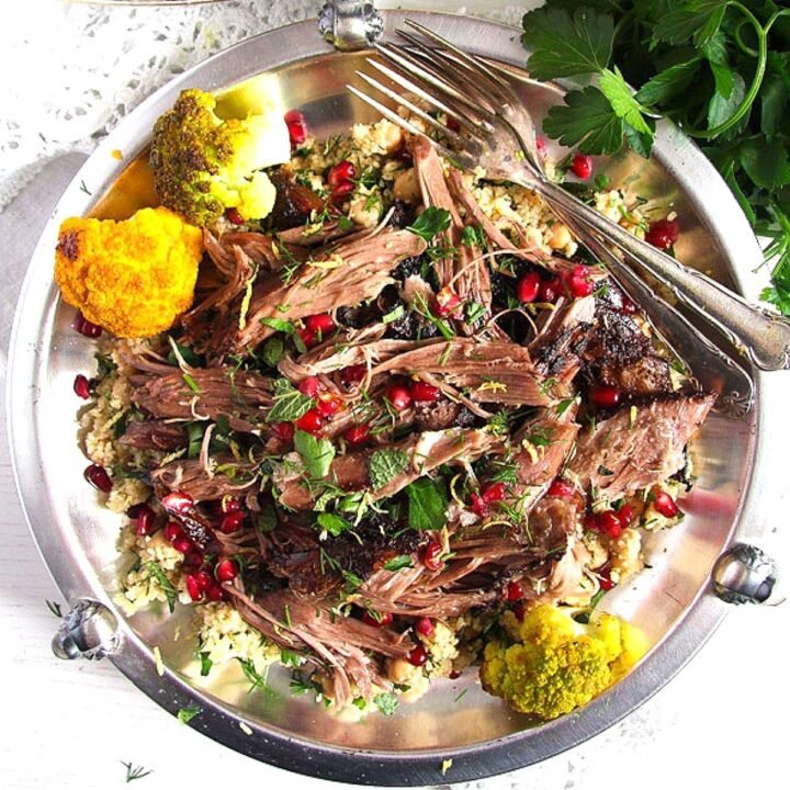 shredded lamb shoulder with pomegranate on a silver plate.