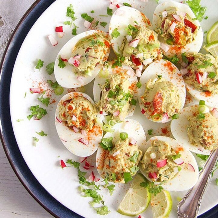 spicy deviled eggs close up on a plate with lime wedges.