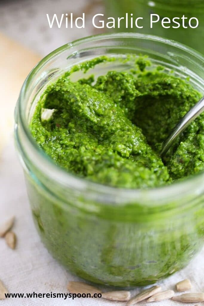 green pesto in a jar with a spoon in it