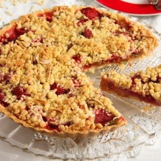 rhubarb crumble pie with strawberries and streusel on a platter