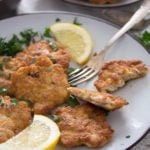 plate with chicken breast fritters and lemon wedges