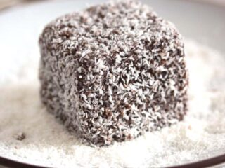 lamington cake close up on a white plate with coconut flakes around it