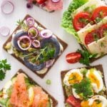 danish sandwiches with cheese, tomatoes, salmon, herring, eggs on black bread
