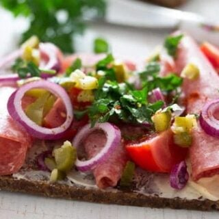 open sandwich with salami, red onions and tomatoes