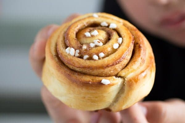 Swedish kanelbullar cinnamon bun held by a child