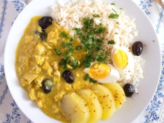 aji de gallina served with potatoes, hard-boiled eggs and rice