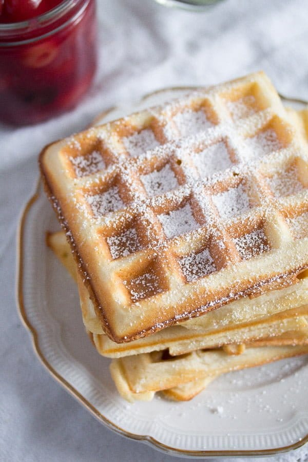 stack of Belgian waffles with icing sugar