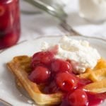 german-style waffle served with cherries and whipped cream