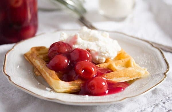 german waffle topped with cherries and cream on a vintage plate