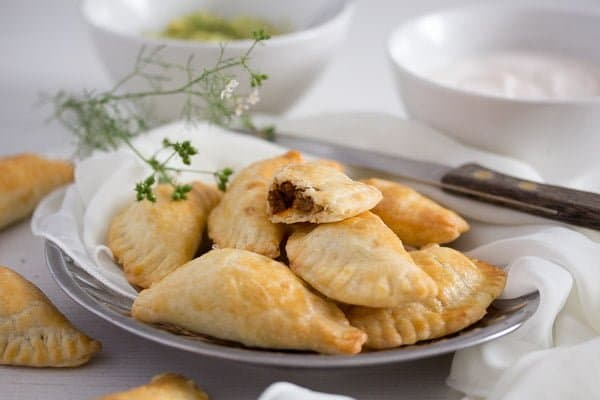 spicy beef empanadas on a serving plate with bowls behind