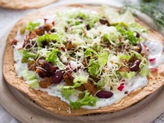 chorizo tostadas with beans on a wooden board.